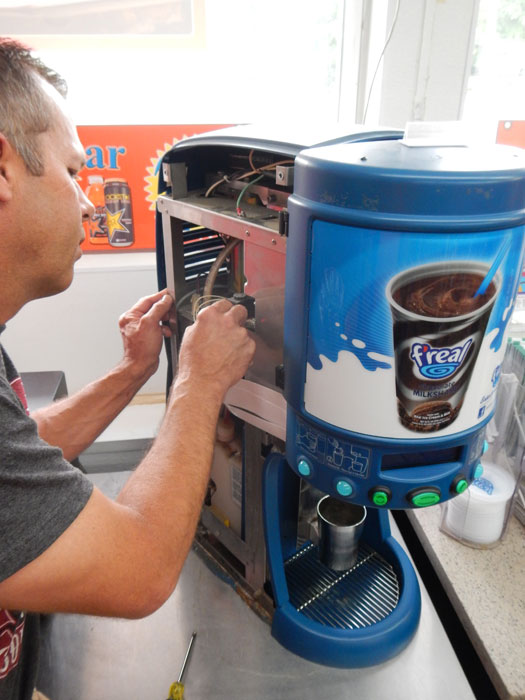 Mainstreet Property Services tech repairing commercial coffee maker