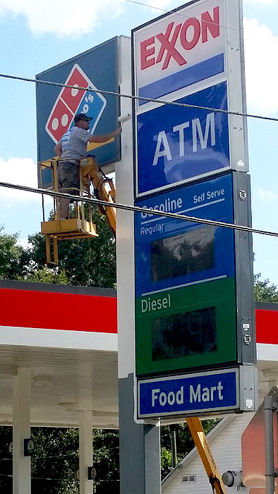Mainstreet Property Services tech on extended boom painting top of Exxon gas station sign